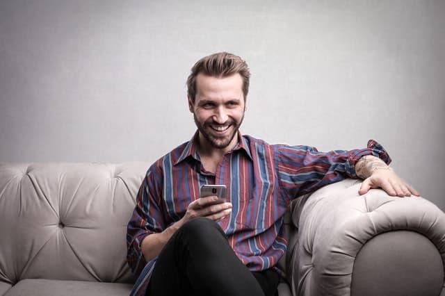 גבר יושב ומשחק בפלאפון