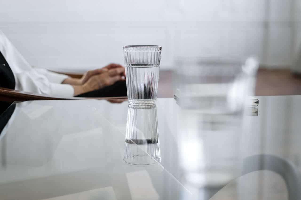כוסות מים על שולחן זכוכית ואיש יושב